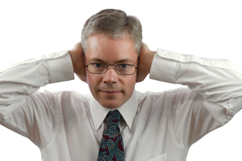 A businessman covering his ears.