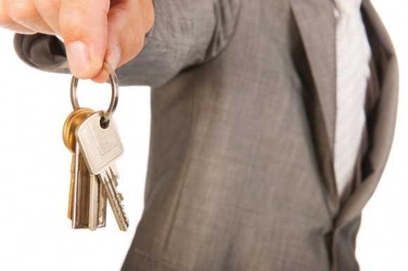 A businessman holding a set of keys in front of him.