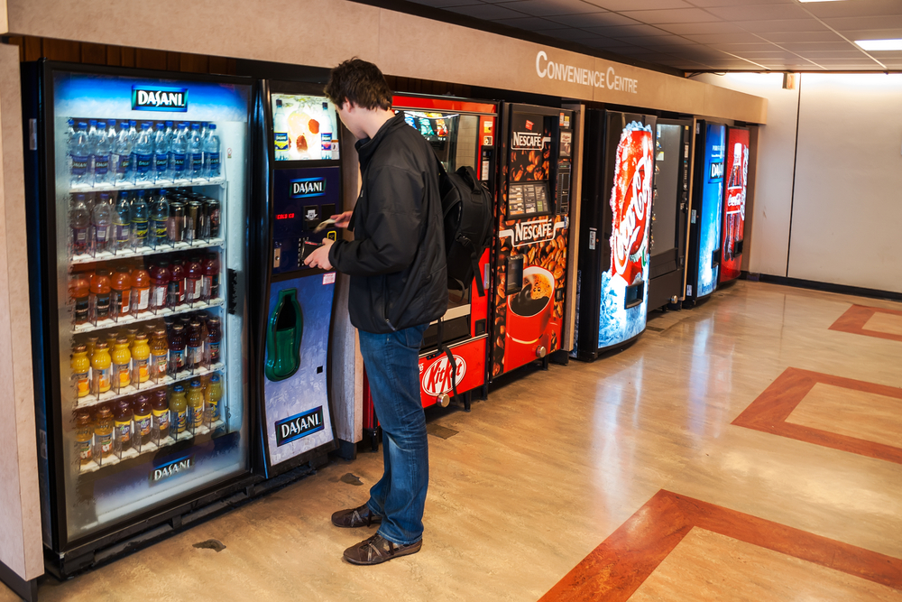 A customer making a purchase at a vending machine.